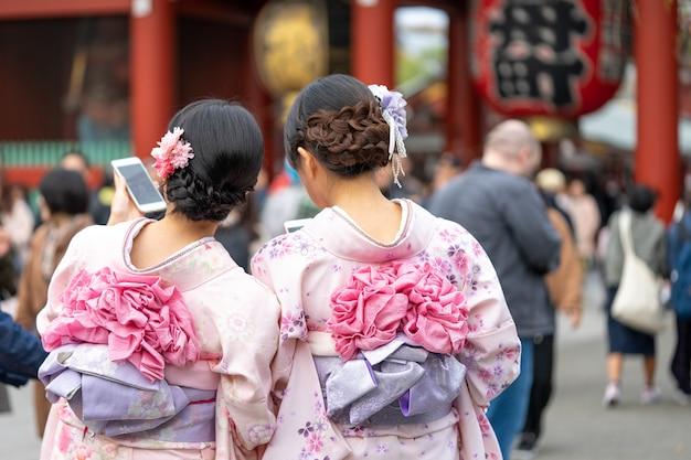Chica joven que lleva el kimono japonés que se coloca delante del templo de sensoji en tokio, japón.