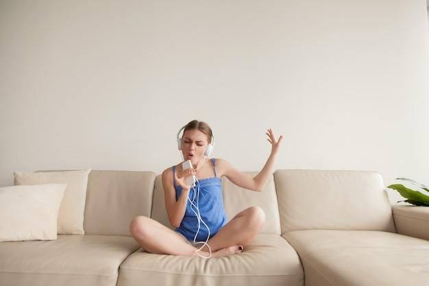 Chica joven que lleva música que escucha de los auriculares en smartphone en casa