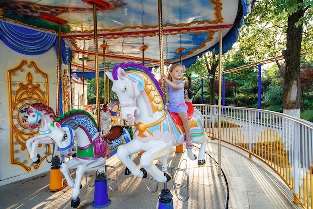 Chica joven que monta en caballo del parque de atracciones en el paseo de la diversión del carrusel en el parque de los parques de atracciones al aire libre