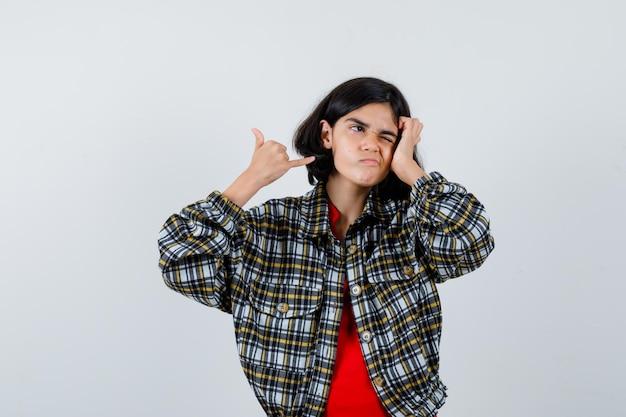 Chica joven que muestra el gesto de llamarme en camisa a cuadros y camiseta roja y lucir linda, vista frontal.