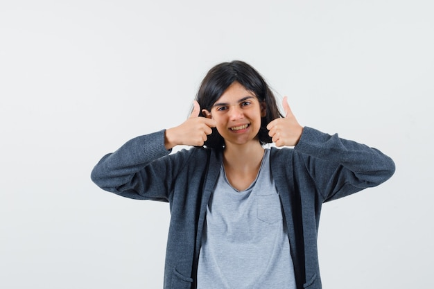 Chica joven que muestra los pulgares dobles hacia arriba en una camiseta gris claro y una sudadera con cremallera frontal gris oscuro y se ve linda.