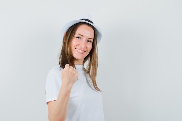 Chica joven que muestra el puño cerrado en camiseta blanca, sombrero y con suerte. vista frontal.