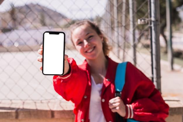 Chica joven que muestra smartphone en parque
