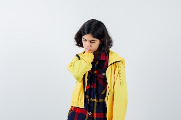 Chica joven que pone la mano en el cuello con camisa a cuadros y chaqueta amarilla y parece cansado. vista frontal.