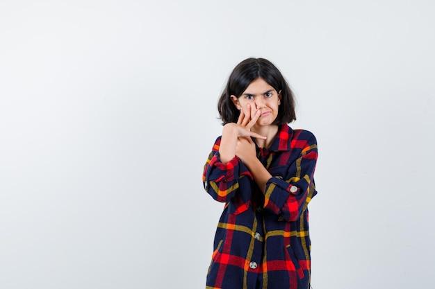 Chica joven que pone la mano en la mejilla mientras sostiene una mano en el cuello en camisa a cuadros y mira seria, vista frontal.