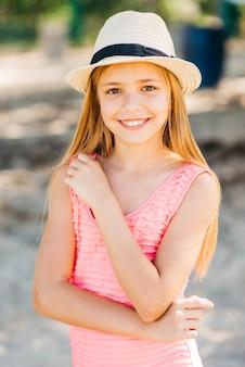 Chica joven que presenta con la mano en el pecho en la playa