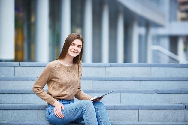 Chica joven que se sienta en los pasos y que mira en la tableta.