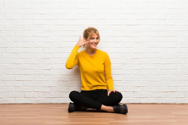 Chica joven que se sienta en el suelo que hace gesto del teléfono. vuelve a llamarme señal
