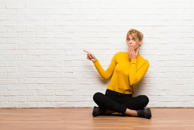 Chica joven que se sienta en el suelo que señala el dedo al lado con una cara sorprendida