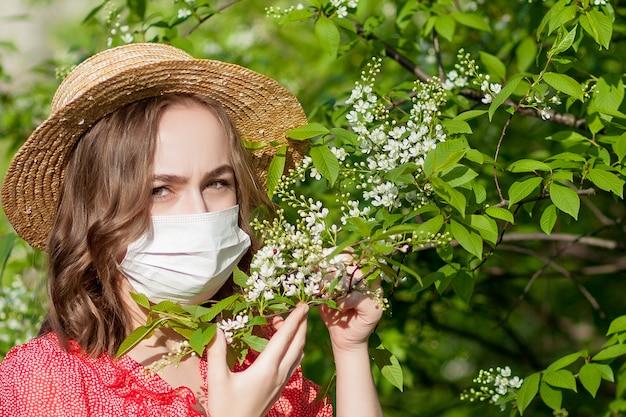 Chica joven que sopla la nariz y estornudos en el tejido delante del árbol floreciente. alergenos estacionales que afectan a las personas. bella dama tiene rinitis.