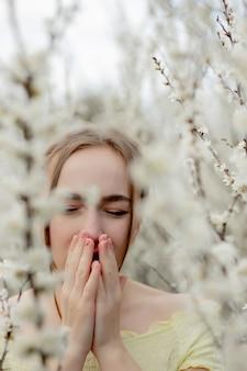 Chica joven que sopla la nariz y estornudos en el tejido delante del árbol floreciente. alergenos estacionales que afectan a las personas. bella dama tiene rinitis