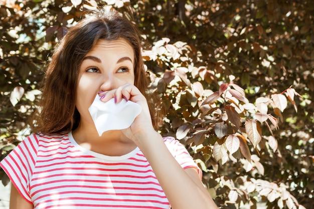 Chica joven que sopla su nariz. chica joven con alergia en parque del otoño