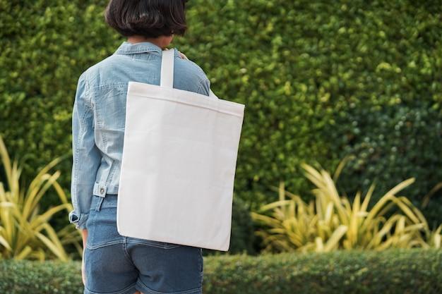 Chica joven que sostiene el bolso blanco de la tela en el parque