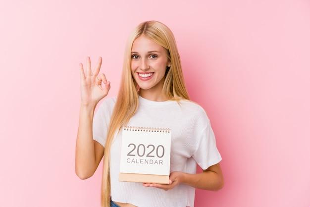 Chica joven que sostiene un calendario 2020 alegre y confidente que muestra gesto aceptable.