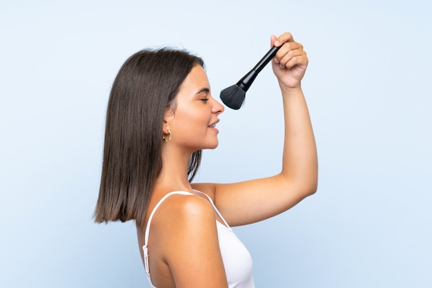 Chica joven que sostiene el cepillo del maquillaje sobre la pared aislada