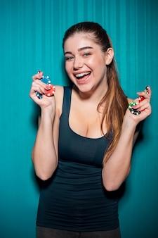 Chica joven que sostiene fichas de póker en azul