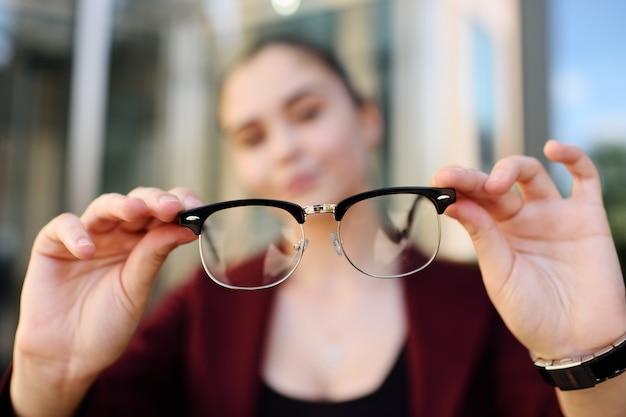 Chica joven que sostiene el primer de los vidrios. óptica, blzorukost, hipermetropía, astigmatismo.