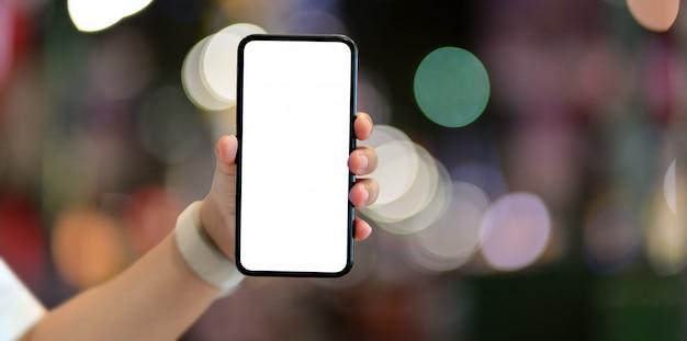Chica joven que sostiene el teléfono inteligente de pantalla en blanco