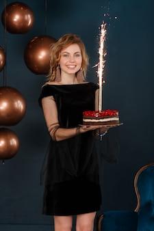 Chica joven que sostiene la torta de cumpleaños con el fuego artificial ardiente en fondo negro de la pared.
