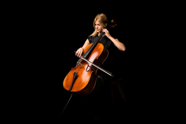Chica joven que toca el violoncelo en fondo negro aislado