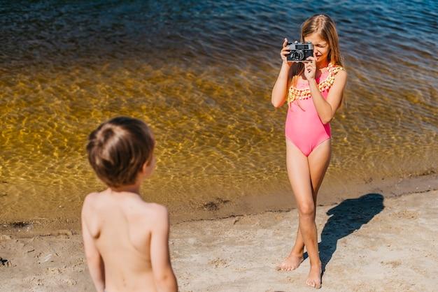 Chica joven que toma la foto del hermano de pie en la playa del mar