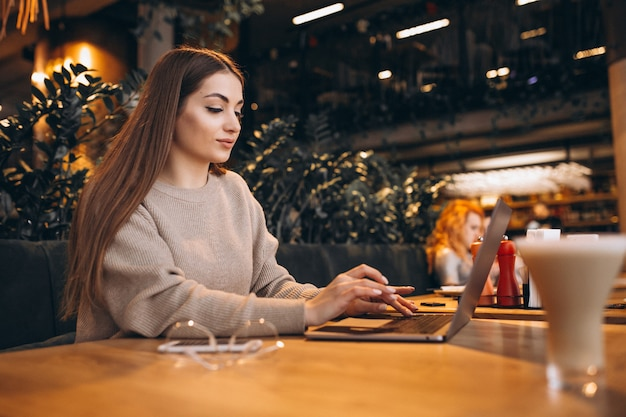 Chica joven que trabaja en una computadora en un café