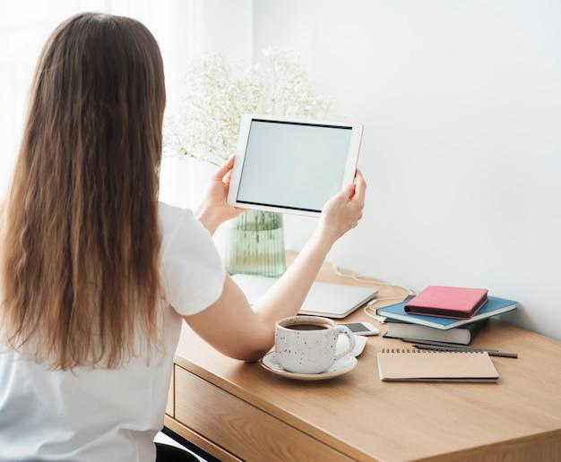 Chica joven que trabaja en la oficina en casa en la mesa