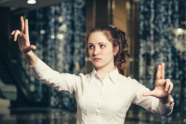 Chica joven que trabaja con un panel táctil virtual en la pantalla. mujer de negocios interactúa con la interfaz holográfica en el cristal invisible.