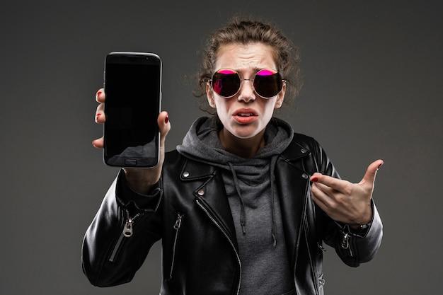 Chica joven con rasgos faciales ásperos, cabello castaño acariciado, manicura brillante, bicicleta gris, chaqueta negra, se muestra en el teléfono y no está contenta