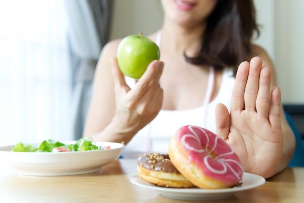 Chica joven rechazando comida chatarra como donas.