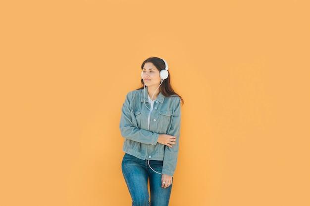 Chica joven relajante escuchando música con sus auriculares de pie frente a una pared amarilla