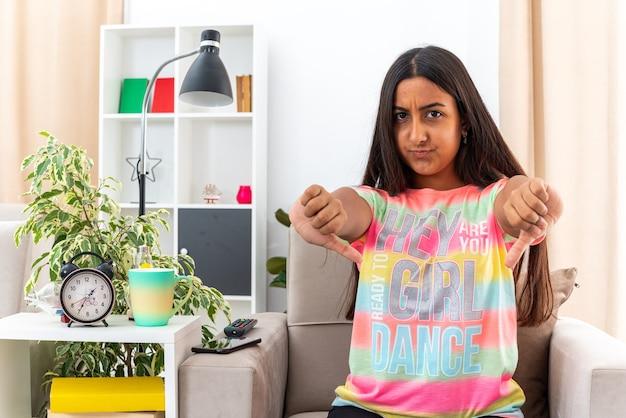 Chica joven en ropa casual mirando con el ceño fruncido serio mostrando los pulgares hacia abajo sentado en la silla en la sala de luz