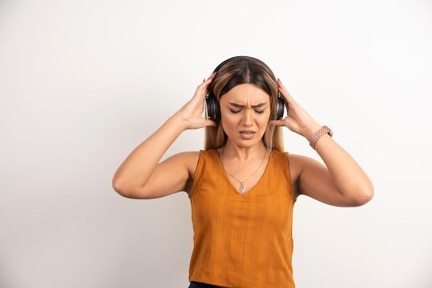 Chica joven en ropa casual posando con auriculares.