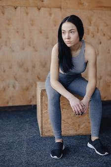 Chica joven en ropa deportiva en un gimnasio en un fondo simple, un tema de fitness y deporte