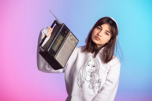 Chica joven en ropa deportiva y peinado corto sosteniendo una radio vintage.
