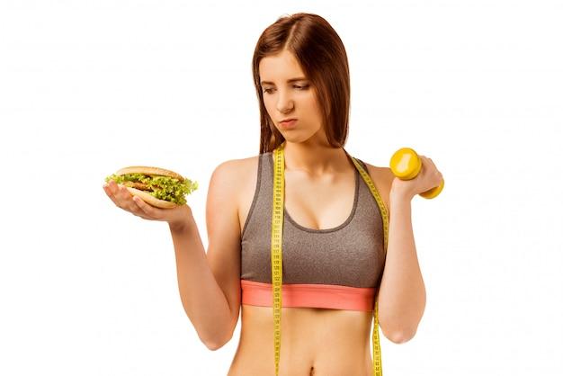 Chica joven en ropa deportiva, sosteniendo pesas.