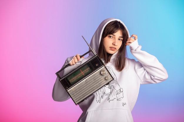 Chica joven en ropa deportiva sosteniendo una radio vintage y escuchando música.