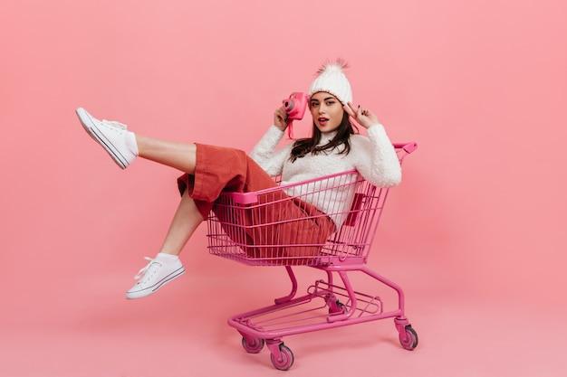 Chica joven en ropa tejida posa con cámara rosa mientras está sentada en el carro del supermercado en la pared aislada.