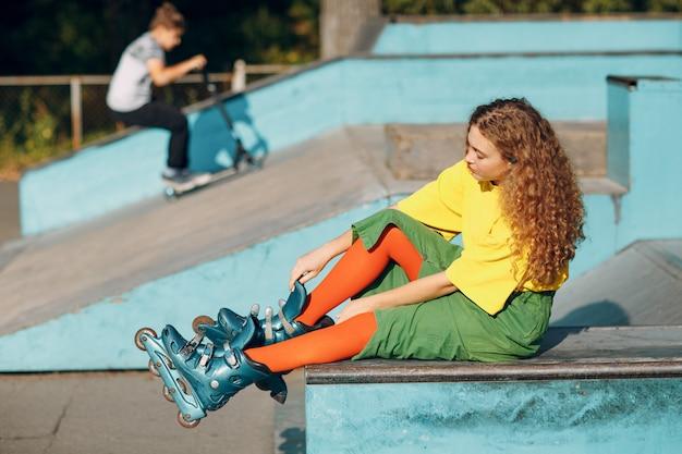Chica joven en ropa verde y amarilla y medias naranjas con peinado rizado patinaje sobre ruedas sentado en skate park