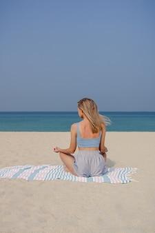 Chica joven rubia practica yoga y meditación en la posición de loto en la playa en un día soleado.