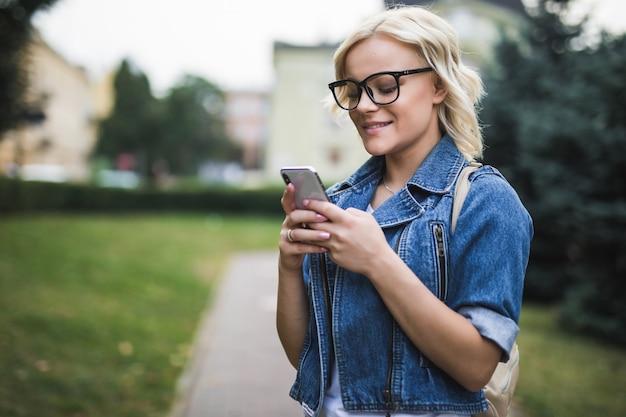 Chica joven rubia usa el teléfono para desplazarse por la conversación de la red social en la mañana de la plaza del otoño de la ciudad