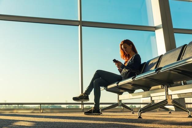 Chica joven en la sala de espera de la estación.