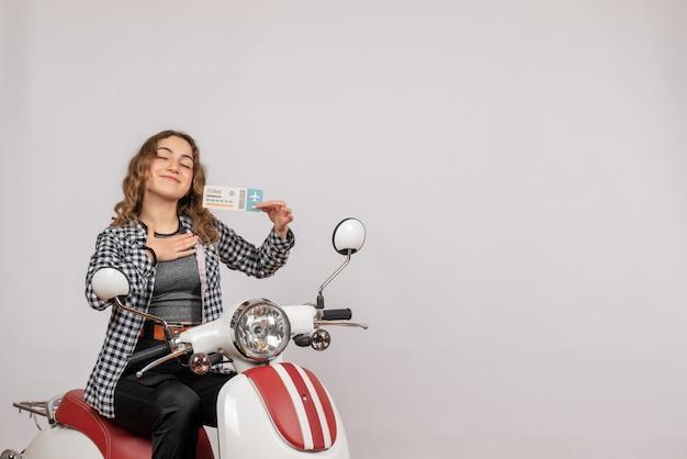 Chica joven satisfecha en ciclomotor con billete en gris