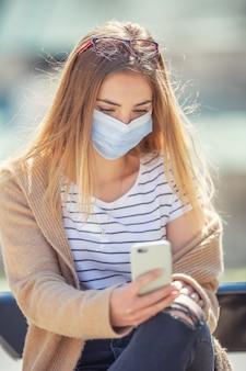 Chica joven sentada al aire libre enviando mensajes de texto en un teléfono móvil con mascarilla protectora.