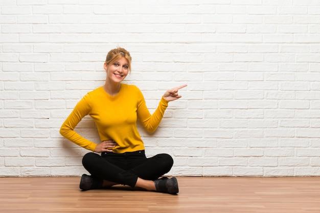 Chica joven sentada en el suelo apuntando el dedo hacia un lado y presentando un producto