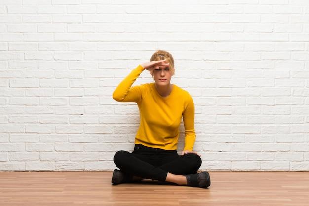 Chica joven sentada en el suelo mirando lejos con la mano para mirar algo