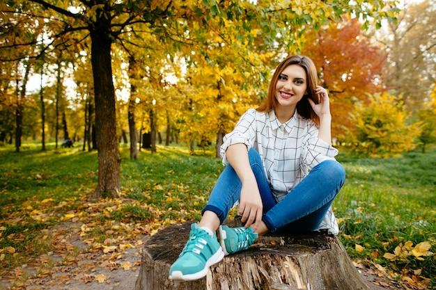 La chica joven se está sentando en un tocón en el parque del otoño.