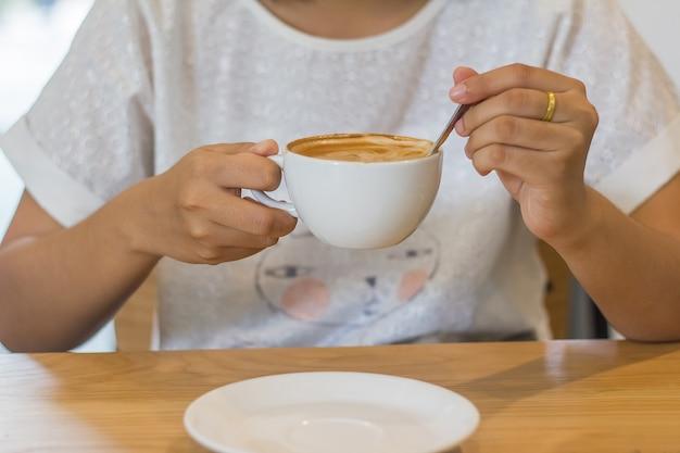 La chica joven está sentando y tomando café del latte en la cafetería.