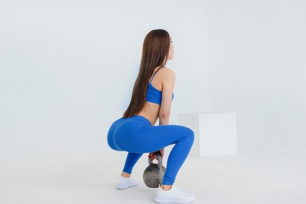 Chica joven sexy realiza ejercicios deportivos en una pared blanca. fitness, estilo de vida saludable.