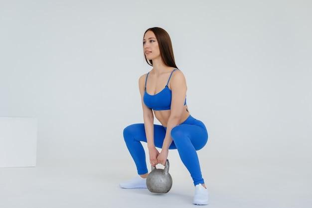 Chica joven sexy realiza ejercicios deportivos